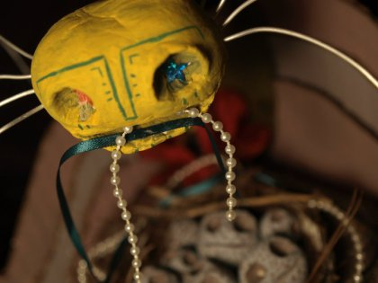 yellow spider beads & ribbon in mouth above nest of head eggs